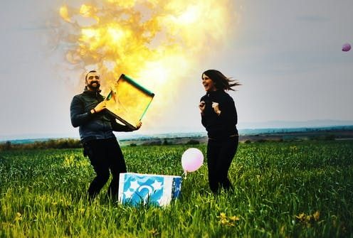 With his excited wife looking on, a man opens a box as a flame shoots out of it.