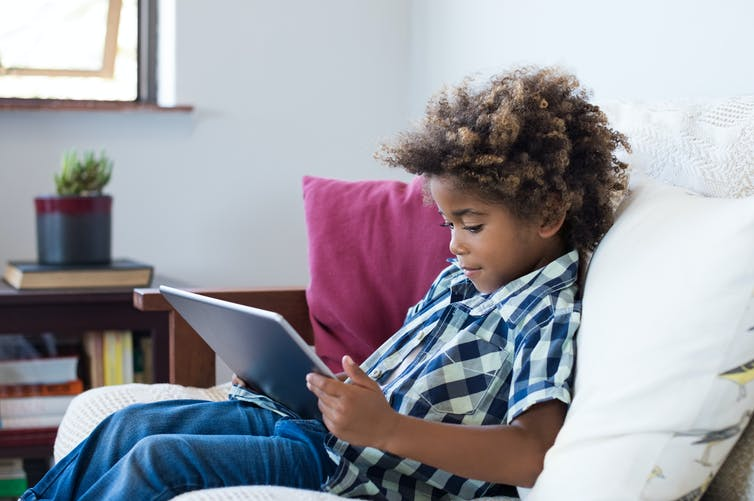A young black boy using a tablet sits on a sofa