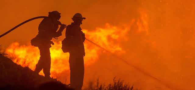 Two firefighters steady a hose on a hillside, spraying water on flames below.