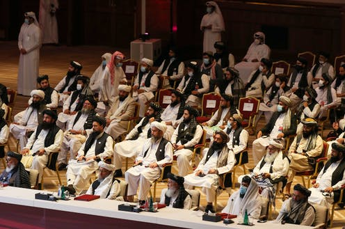 Dozens of Taliban members sit in an auditorium-style setting