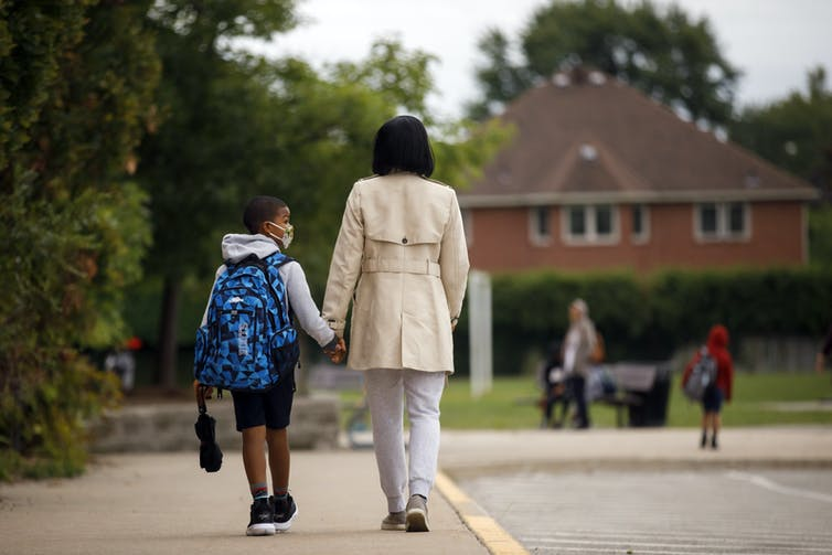 A boy and his mother seen from behind walking to school.