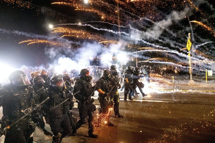 Police in riot gear and carrying weapons walk in a line as the plumes from tear gas cannisters are seen behind them.