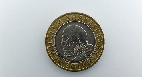 A coin showing a skull and rose.