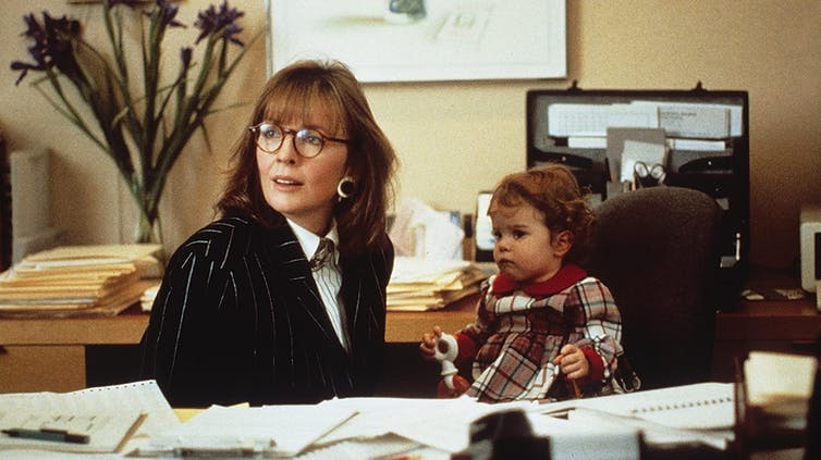 Movie still. Diane Keaton and a baby at a desk.