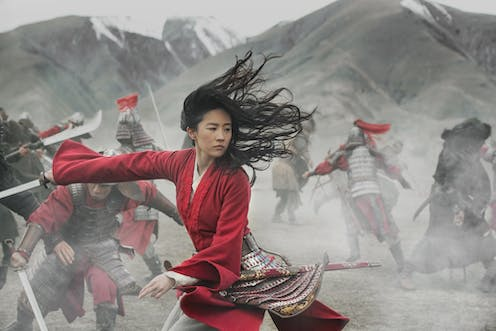 Mulan, in red, holds a sword in battle