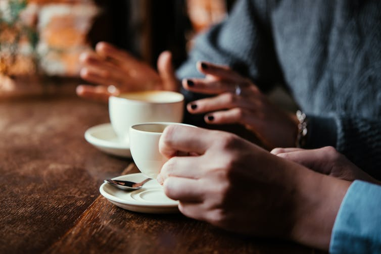 Two women in a cafe talking and having coffee. Image focuses on their cups and hands.