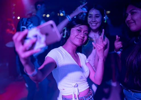 Three young women dancing and taking a selfie at a nightclub.