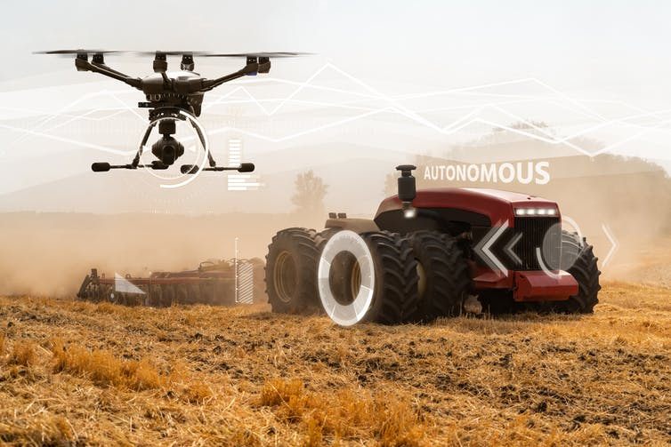 Driverless tractor and drone pass over a field.