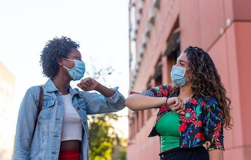 Two women wearing masks elbow bumping