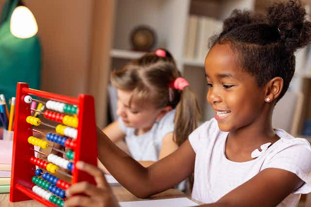 Young girl counting on an abacus