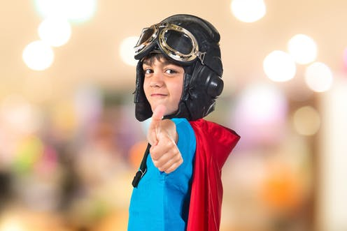 Boy wearing a superhero costume and aviator glasses doing a thumbs up