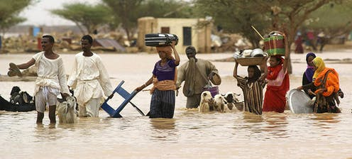 People carrying belongings on their heads and leading goats walk through flooded area