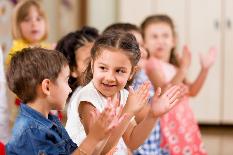 Kids likely in a childcare centre clapping hands