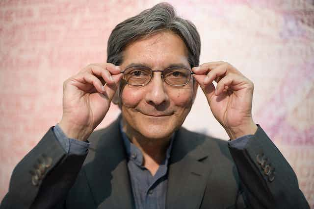 A man in suit jacket grey shirt smiles playfully as he looks into camera holding the sides of his spectacles.