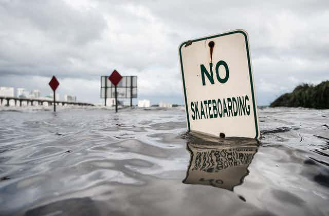 A 'no skateboarding' sign under water along the St. Johns River in Jacksonville, Florida, during Hurricane Irma.