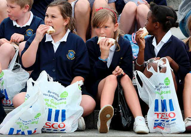 Three children sittiing on the ground eat sandwiches with Tesco bags at their feet.