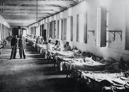 Two men standing next to row of men in hospital ward.