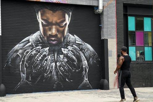 A man photographs a mural on the street.