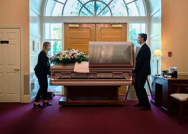 Two people position a casket in a funeral home