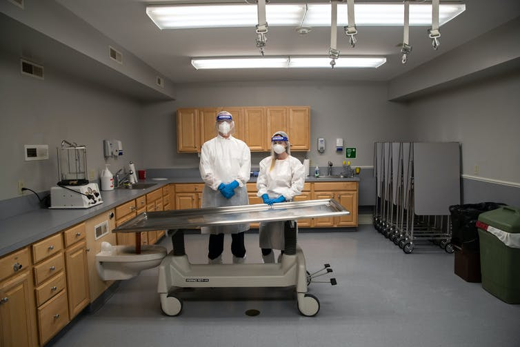 Two funeral home staff stand behind a mortuary table