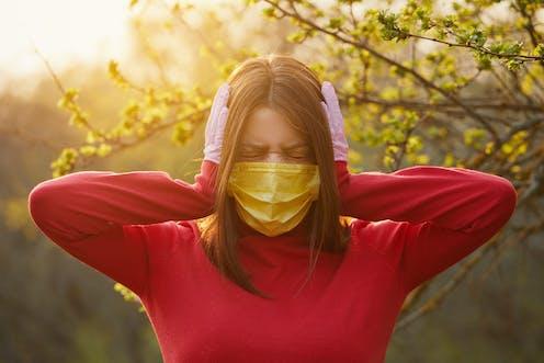 Una mujer con mascarilla amarilla y guantes sanitarios rosas se tapa los oídos con gesto de no desear oír nada.