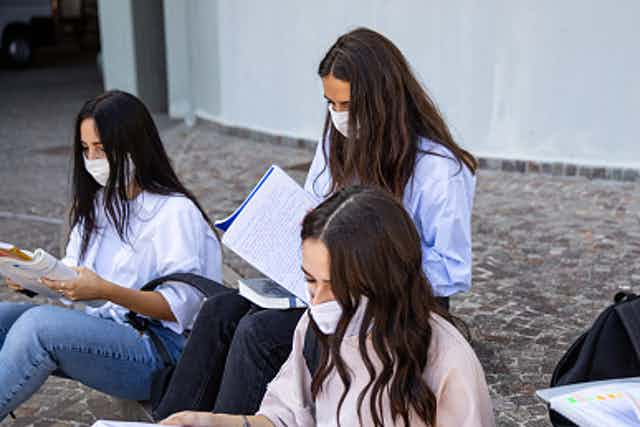 A group of female students sit outside reading notebooks as they wear masks.