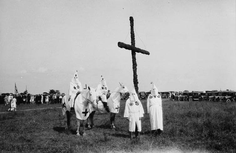 Hooded figures stand in front of a cross