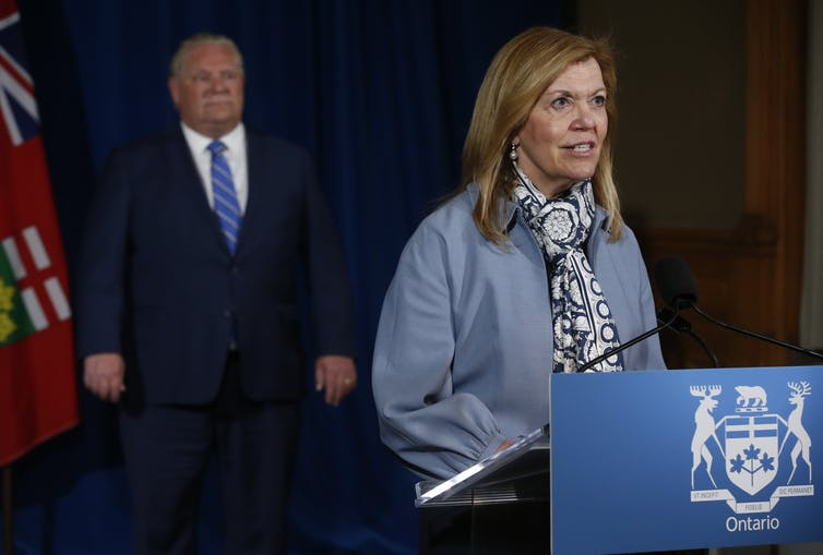 Ontario Premier Doug Ford looks on as Ontario Health Minister Christine Elliott stands at a podium