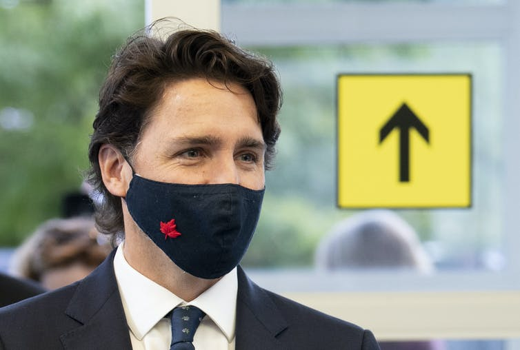 Justin Trudeau, wearing a mask, walks into a building with a sign that shows an arrow pointing up behind him.