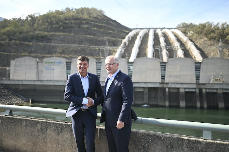 Scott Morrison and Angus Taylor shake hands in front of Snowy Hydro