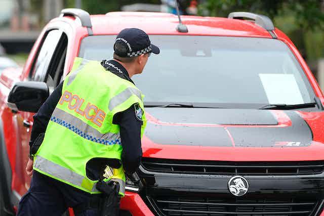 A police officer checks a car on the Queensland border
