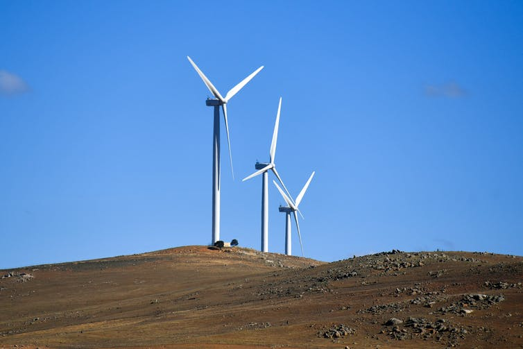Wind turbines against a blue sky.