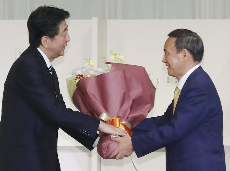 Shizo Abe and Yoshihide Suga holding a bunch of flowers.