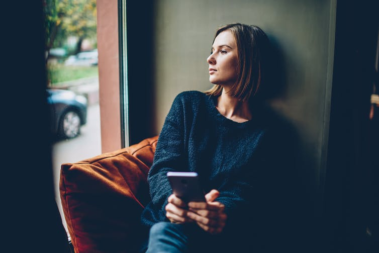 Woman holding phone, looking out a window.