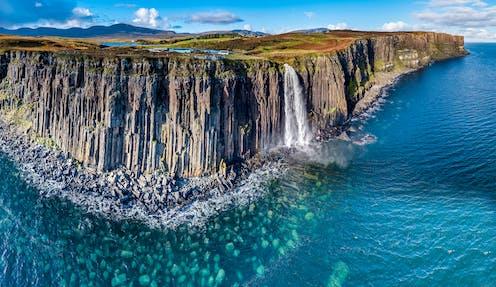 The sheer coastline of the Isle of Skye with blue, shallow coastal water.