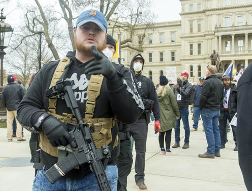 Man carrying rifle stood in front of protestors