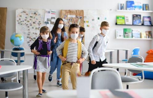 Cinco niños y niñas con mochila y mascarillas entran en un aula.