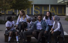 Group of girls in school uniform sitting on a bench.