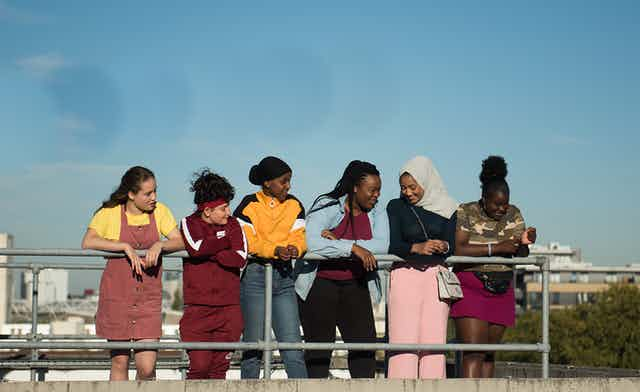 Group of girls look out on a city.