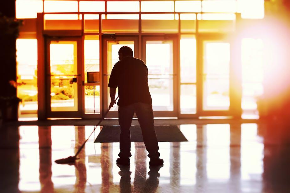 Man mopping hallway floor.