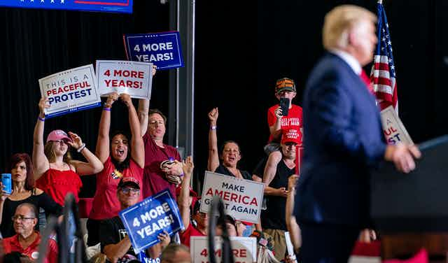 Trump supporters wave signs reading Four More Years and Make America Great Again as Donald Trump speaks behind a podium.