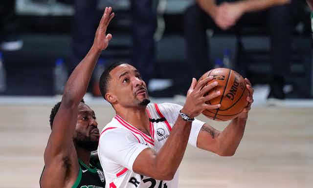 A basketball player prepares to throw the ball with another player behind him.