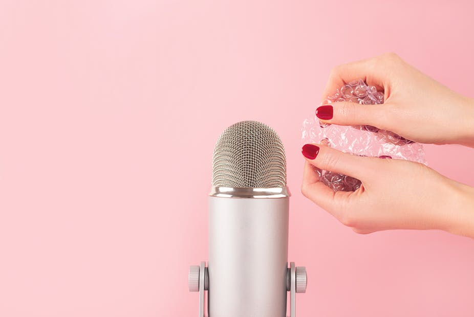Woman with painted nails pops bubble wrap beside a microphone.