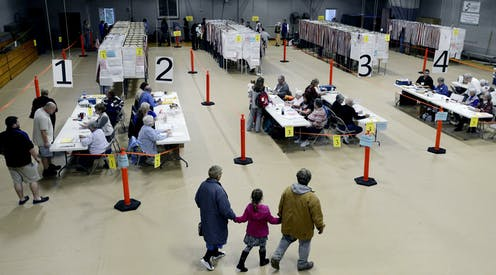 Poll workers sit at long tables checking in voters in a cavernous, auditorium-type space