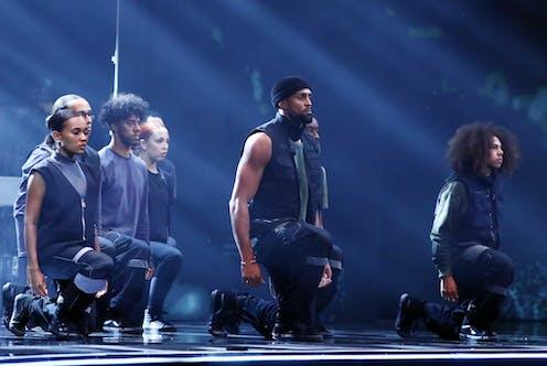 Group of dancers in black kneeling on one knee with their eyes closed.