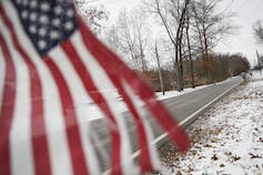 A tattered American flag is flown from a mailbox.