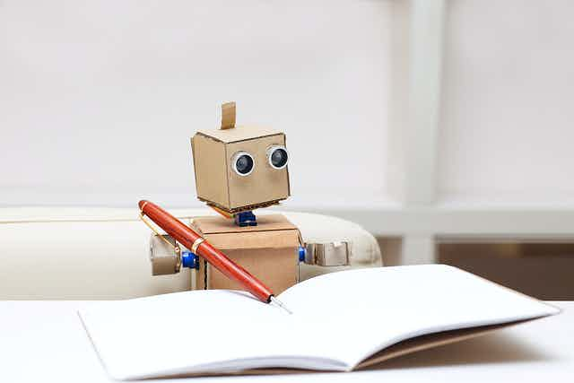 Small cardboard sat at a desk with pen and notepad