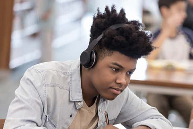 A young African American boy writes on a notebook while reading on his laptop with a headset on.