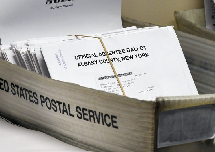 Mailed ballots sit in a box.