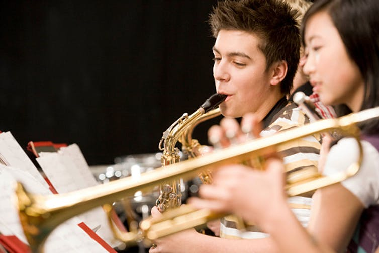 Two students play the saxophone while reading sheet music.